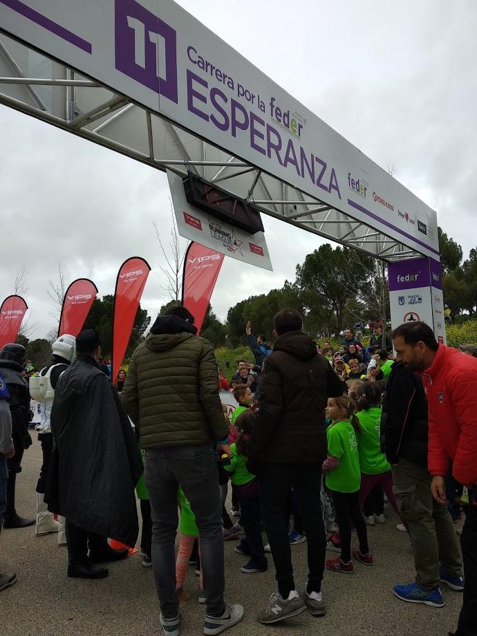 Imagen de la meta con el cartel de llegada de carrera por la esperanza y un grupo de niños